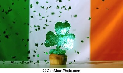 Shamrock confetti falling on cup cake