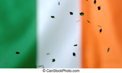 Shamrock confetti falling on irish flag background in slow...