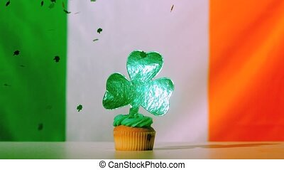 Shamrock confetti falling on st patricks day cupcake on...