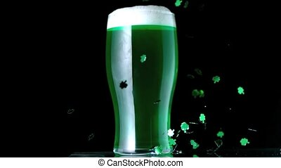 Shamrock confetti next to a pint of green beer in slow...