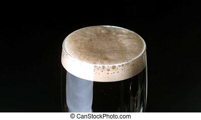 Shamrock landing on head of pint of stout on black...