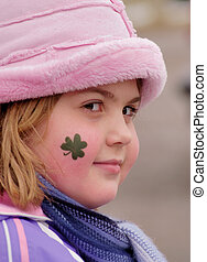 Shamrock on cheek - Young girl with painted shamrock on her...