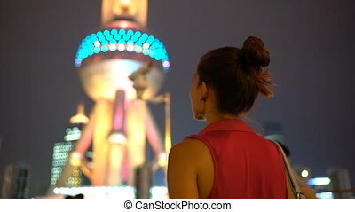 Shanghai business woman walking under the city lights at night by Oriental Pearl Tower in Pudong, China. Multicultural Asian Chinese / Caucasian young woman professional in financial district.