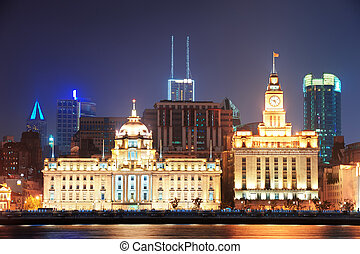 Shanghai historic architecture at night lit by lights over...