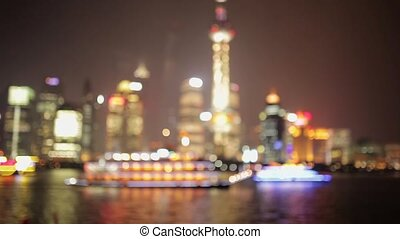 SHANGHAI - MARCH 19, 2018: Defocused of  of Pudong embankment at night,Brightly illuminated tourist boat sail at Huangpu river,