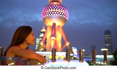 Shanghai woman or tourist looking at city lights at night by Oriental Pearl Tower in Pudong, China. Multicultural Asian Chinese / Caucasian young woman professional in financial district.