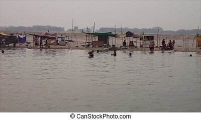 Shanties and locals bathing in Ganga River, India - Wide...