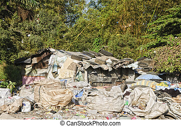 Sacks and sacks of garbage in front of a shanty