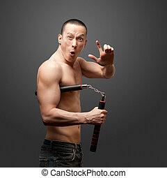 shaolin monk - funny muscular shaolin monk with nunchaku in...