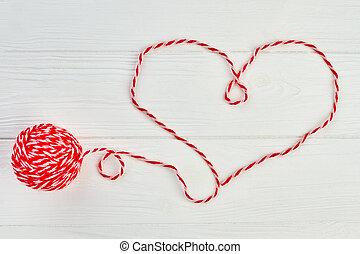 Shape of heart from red woolen thread.