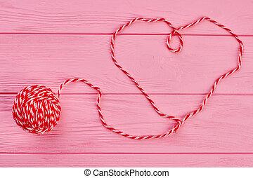 Shape of heart from red woollen thread.