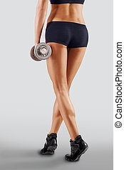 Shapely female legs in sporting black shorts. On a gray