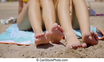 Shapely legs of two young women sunbathing as they sit on...