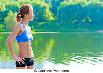 shapely, toned woman in sportswear rest on the nature