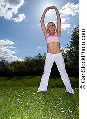 Shapely woman exercising on the grass