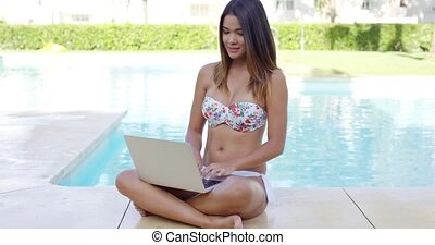 Shapely young woman in a bikini using a laptop