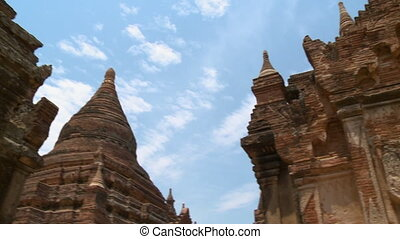 An extreme close up shot of small stupas close to a big stupa on the roof of an ancient building in Burma