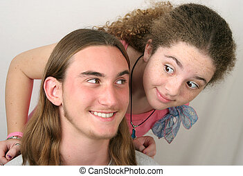 Sharing A Joke - A teenaged girl and boy smiling like they...