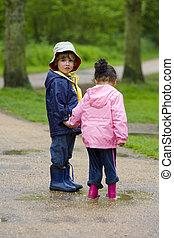 Sharing A Puddle - A little boy and girl wearing wellington ...