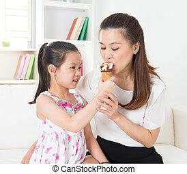 Sharing an ice cream cone - Eating ice-cream. Happy Asian ...