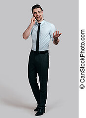 Sharing business ideas. Full length of handsome young man talking on smart phone and gesturing while standing against grey background