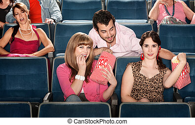 Sharing Popcorn in a Theater - Smiling ladies sharing ...