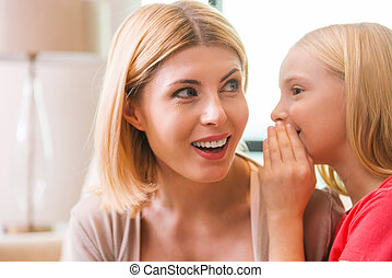 Sharing secrets with mom. Happy mother and daughter sharing...