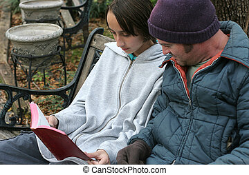 Sharing The Word - A teen volunteer reading the bible to a...
