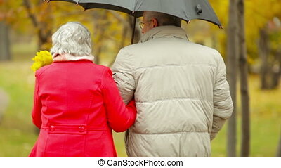 Sharing Umbrella - Couple of retirees sharing an umbrella...