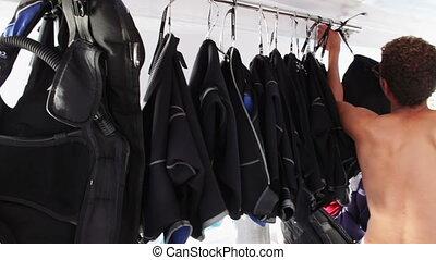 Sharm el-Sheikh, Egypt - December 6, 2016: man chooses costume for diving