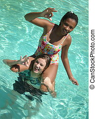 A picture of two girls in the swimming pool with one on the shoulders.