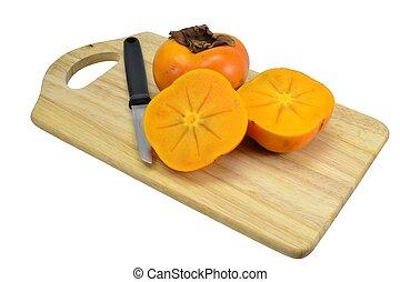 Sharon persimmon fruit sliced on wooden board