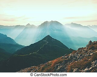 Sharp Alps peaks, rocks without people. View over Alpine rocks above deep vallyes to far horizon