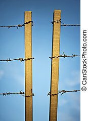 sharp barbed wire with two concrete columns on blue sky background