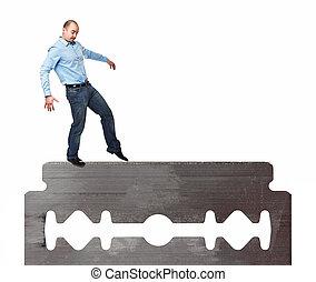 sharp business - man try to walk on razor blade