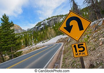 Sharp Curve Road. Colorado Mountain Highway and Sharp Curve Warning Sign.