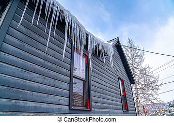 Sharp icicles on the snowy roof of a home with weathered wooden exterior wall