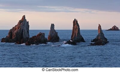 Sharp islets at evening (Asturias, Spain). - Small waves...
