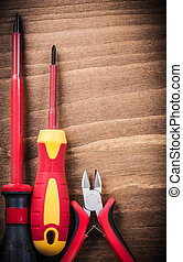 Sharp nippers insulated screwdrivers on wooden board ...