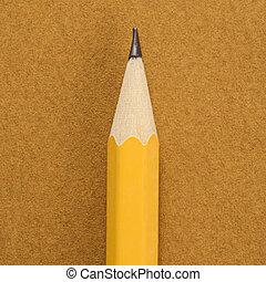 Sharp pencil. - Close up of sharp pencil tip on tan...
