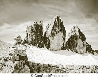 Sharp stones stacked into pyramid. Mountain ridge in Italian...
