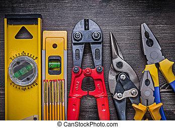 Sharp tin snips steel cutter pliers construction level wooden meter.