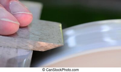 Sharpening a chisel on a stone whee - Water stone used to...