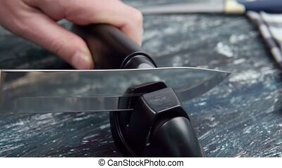 man is sharpening kitchen knives. sharpening a knife with a home sharpener