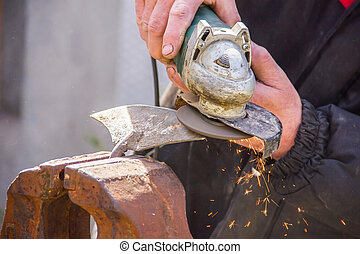 sharpening garden tools hoe using grinder close-up, Machine...