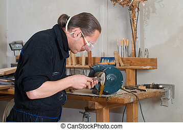 Sharpening - Young carpenter sharpen chisel on grinding...