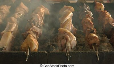 Shashlik being cooked close up. Juicy meat on brazier. Pork...