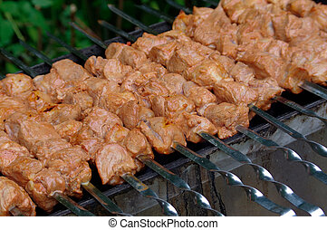 Shashlik on skewers closeup, raw and cooked