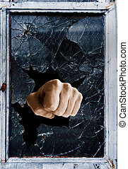 Fist punching through a shattered glass window