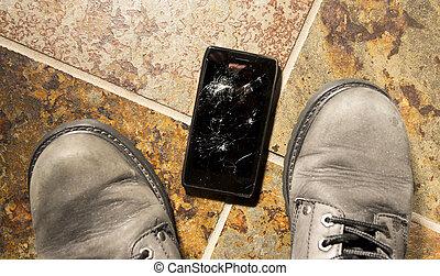 Shattered Smartphone - A smartphone lies broken between the...